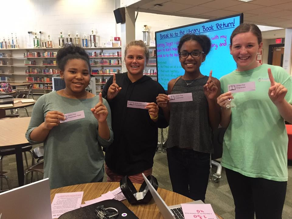 Four female middle school students show they are first to break out of the library.