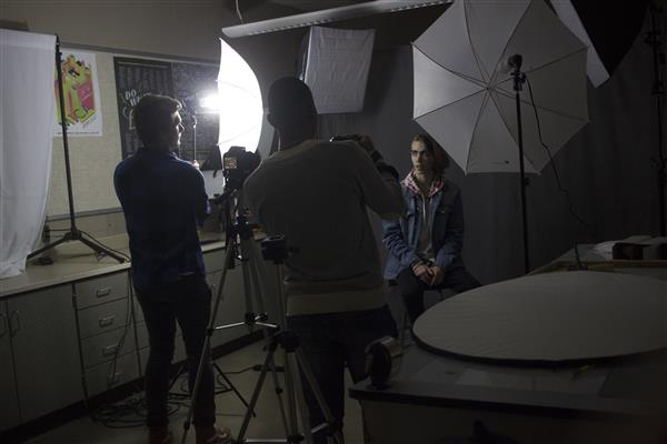 Three high school students use studio lighting equipment to take pictures.