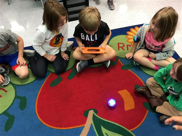 Five students look on as a student uses an ipad to drive a Sphero robot.
